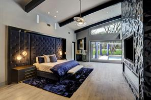 The master bedroom is anchored by a recessed, tufted headboard which is flanked by pendant reading lights. Picture and transom windows provide an abundance of natural light and views of the grounds, pool and covered entertaining space.