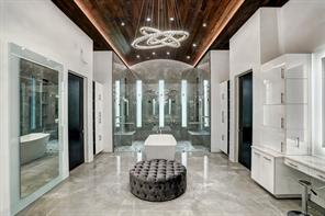 The master bathroom, is outfitted with a barreled ceiling, dual vanities, and a backlit mirror. The bathroom centerpiece is a Bain Ultra soaking tub with a handheld spray as well as tub filler. The oversize master shower is fitted with 14 heads – 2 handheld, 8 body jets, and 4 overheads.