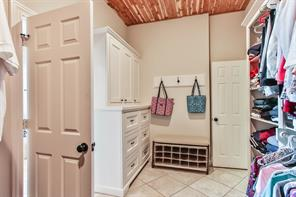 Master closet with cedar-lined ceiling and access to the laundry room