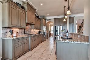 Entertainer's kitchen with stainless appliances, service bar, walk-in pantry, and large island.