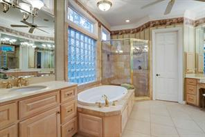 Master bath with dual sinks and whirlpool tub and separate shower.