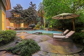 The beautiful backyard offers a resort style pool with waterfall feature, hot tub, side yard and grassy area.