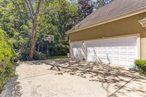 Three car garage with a workshop and a wide driveway and a driveway gate and built-in basketball hoop--a great play area