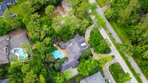 Aerial view of 11905 Heritage Lane.  Notice the circular drive, wooded lot with mature trees, wide driveway, grassy area behind garage, trees on the west side of the home make hard to see the side yard on the west side, and lovely pool.  Come see the great home!