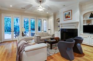 The spacious family room enjoys views of the lush backyard and sparkling pool.