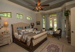 The over-sized master bedroom is luxurious and tranquil. Again, notice the leaded glass transoms for soft natural light. There is a French door that leads to a screened porch. Fabulous ceiling detail in this room lends a dramatic effect.