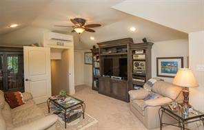 On the second floor above the garage is an extremely large bonus room. There are multiple built ins in this space, including a desk, credenza, shelving, lighted gun case, bookcase and storage drawers.