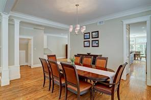 Located off the living room is the dining room with a 6-light chandelier, crown molding, wood floors and neutral paint.