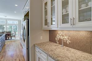A butler's pantry with glass front cabinets and granite countertop connects both the kitchen and dining room and accesses the large walk-in pantry.