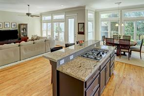The kitchen features a breakfast bar, granite counters, gas cooktop and wood floors.