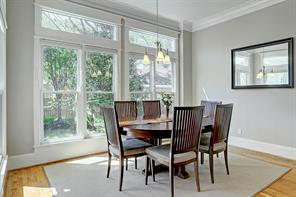 Crown molding, 3-light chandelier, transom windows, neutral paint and wood floors are features in the breakfast room.