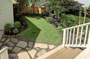 The backyard has fresh landscaping with pavers to an oversized garage.