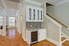 A wet bar with glass front shelving is located off the den and dining room.