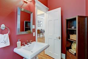 The powder room featuring a pedestal sink is conveniently located off the den and dining room.
