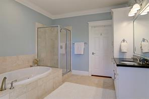 The master bath has recessed lighting, crown molding, separate tub and shower with tiled wall surround, dual vanities with granite countertops, tile flooring and a private water closet.