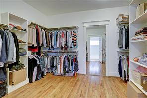 The expansive master closet has built-in shelving and a full length framed mirror.
