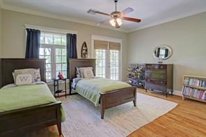 This secondary bedroom has access to the covered front balcony, crown molding, a ceiling fan,  neutral paint and wood floors.