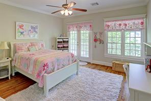 A third secondary bedroom has access to the covered front balcony, crown molding, a ceiling fan, neutral paint and wood floors.