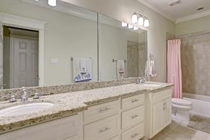 Crown molding, neutral paint, dual sinks with granite countertops and tile floors are featured in the secondary bath.