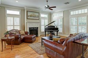 The 23' x 19' living room has recessed lighting, ceiling fan, crown molding, transom windows and plantation shutters. A gas fireplace, neutral paint and wood floors finish the room.