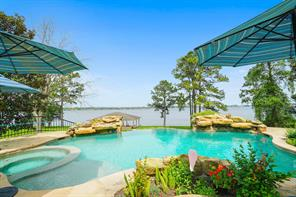 Feast for the eyes!  Gorgeous pool and hot tub with stone accents and landscaping, as well as a fantastic open view of Lake Conroe!