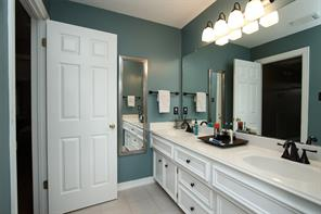 Full bath upstairs with double sinks, updated light and plumbing fixtures.