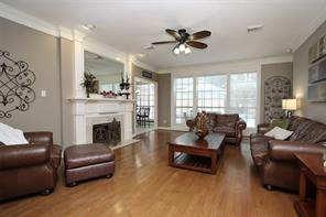 Den features include hardwood floors, view of backyard and pool and classic gas-log fireplace and mantle.