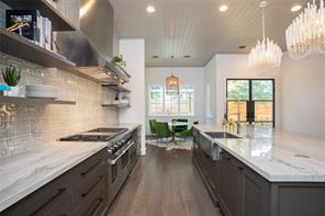 "Kitchen: 10' X 5' island with seating space, hand painted geometric tile backsplash, stainless steel vent hood, cased openings, bead board celling, Wolf 48"" stove, Asko concealed dishwasher, Sub-Zero 48"" refrigerator, sharp microwave drawer, matt black cabinet hardware"