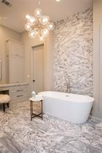 Master Bath: Geronimo marble floors, Geronimo marble wall behind tub, Circa chrome and glass chandelier, recessed lighting, 11' ceiling, Superlative leathered marble counter, dual porcelain sinks, custom cabinets, abundant storage, chrome hardware