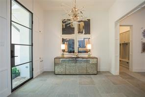 Foyer: Large format sandstone floors, Aidan Gray lucite and brass chandelier, 11' ceiling, wide cased openings, concealed storage