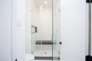 Bath 2: Large shower with steamer glass enclosure, white subway tile, Virginia Mist granite bench, threshold, and shower shelf.