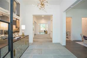 Entry Hall: Large format sandstone floors, Aidan Gray lucite and brass chandelier, 11' ceiling, wide cased openings