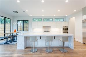 Kitchen: Oversized island with Carrera marble with waterfall edge, clerestory windows for extra light, floating ceiling over island