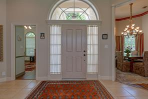 Entryway of the home has generous side light windows plus a large half circle window above the door to let in plenty of natural light. Formal dining is to the right, and the study is to the left.