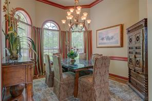 Formal dining area has wood flooring, chair rail, crown molding, and lots of windows to let the light into the home. Lots of room for a large table with multiple pieces of additional furniture.