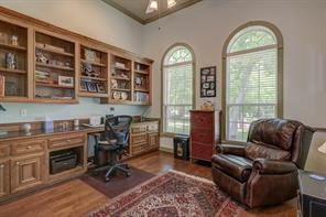 Study has newer wood flooring, and lots of custom built in cabinets and shelving. High ceilings with a fan and large windows here as well. Room could be used as an additional bedroom if needed as there is a spacious closet out of view to the left.