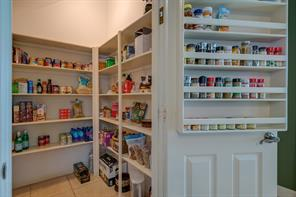 Very spacious walk-in pantry with custom shelving on the door for additional storage of spices.