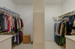 Master closet has tile flooring and lots of storage; custom built-in cabinets on either side are just out of view.