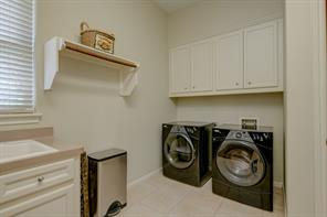 Large utility room has lots of cabinets, a pre-wash sink, and a place for an additional fridge/freezer.