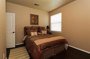 The final bedroom downstairs is also outfitted with the rich wood floors and comfortably holds a queen sized bed.