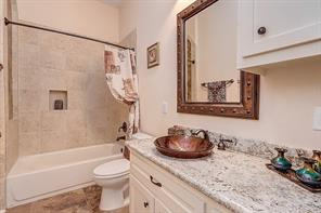 FIRST FLOOR FULL BATH Adjacent to Bedroom Two & serves as the first floor's guest bath. Beautiful granite counters with rich bronze-look glass vessel sink & mirror.