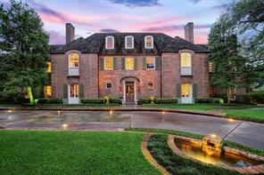 Three-story brick residence on corner lot in highly desirable area of River Oaks, with close proximity to River Oaks Country Club.  Paved front circular driveway with slate blocks, brick seams, paver-lights and brick edging; brick-edged walkways with copper landscape lights lead to custom wrought iron garden gates on each side of the residence.  One of the two illuminated brick-edged water features with spillway fountains is seen in the foreground.