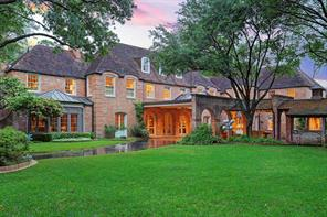 """View of the Rear Elevation at twilight from Left to Right: the brick-edged driveway curves past the bay window in the Family room, French Door in the Living Room and beneath the Lighted Porte Cochere with peaked tempered-glass skylght.  The three arched doors under the Porte Cochere open to the Reception Hall. As you can see there is exceptional """"flow"""" between indoor and outdoor spaces from multiple areas of the grounds and residence for entertaining,  as well as day to day gracious living."""