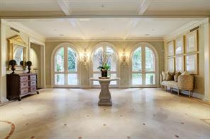 The elegant Foyer and Reception Hall inlaid with rose marble has a painted-paneled ceiling supported by columns, and three sets of 8' tall arched glass French doors with Baldwin® brass hardware and estate-lever handles opening to the Porte Cochere and rear gardens.  Dual 4' wide carved-and-cased openings lead to the Formal Dining Room on one side and a carved-and-cased opening on the opposite side leads to the Formal Living Room (see floor plan).