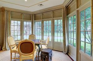 This photograph is a close up of the large (14' x 6') divided light bay window alcove in the Family Room with Fireplace and Wet Bar that provides expansive views of the rear gardens. To the left is a divided light door that opens onto the rear gardens and notice also the extended crown molding cornices above the door and windows that conceal the drapery hardware.