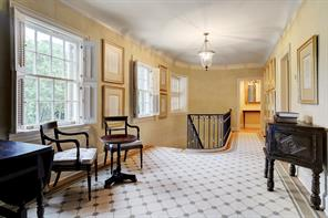 The Second Floor Landing (25' x 10') is illuminated by three tall divided light windows, making it light and bright. Custom balustrade with wrought-iron pickets, gilt knuckles and wrought-iron banister overlooks staircase below. Doors to secondary bedrooms; carved-and cased opening to the Private and Secluded Master Suite and paneled stair hall to the Third Floor.