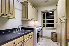 """Laundry - 9' 6"""" x 5' 10"""":  A built-in clothes-folding counter provides convenient workspace above the area for an under-counter full-sized washer and dryer. Wall-mounted cabinetry, drip-dry hanging bar and deep stainless steel soaking sink add flexibility and functionality to this room.  Seen on the right are two tiers of built-in storage cabinets; the divided light window overlooks the East Pocket Garden."""