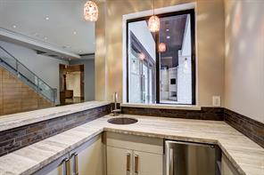 Wet bar off the den with window pass through to outdoors.   Sink, storage and ice maker included.   Beautiful stone countertops with custom backsplash.