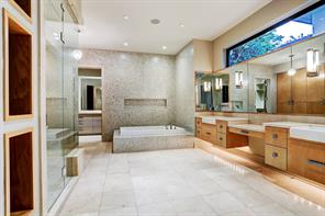 The luxurious Master Bath has double sinks, plenty of storage, stone floors, designer tile walls, steam shower, air jet tub and an abundance of custom storage.