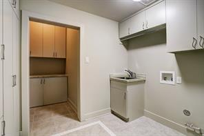 Huge utility room with lots of storage, sink and tile floors.
